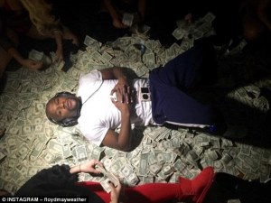 2F8CBE1400000578-0-Floyd_Mayweather_lays_down_on_a_bed_of_dollar_bills_in_LA_as_wom-a-112_1450700371629